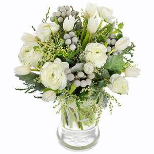 Bukett med blandade vita blommor och gröna blad. Ur Euroflorists sortiment av julblommor.