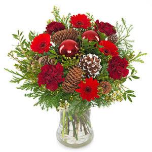 Bukett med röda nejlikor, röda gerberas, kottar, julkula och grönt. Skicka julbuketten med ett blomsterbud från Euroflorist och önska God Jul!