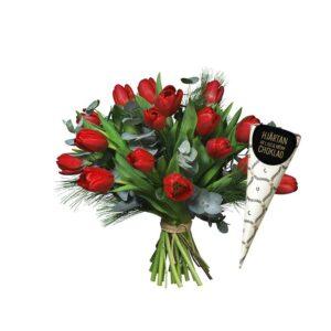 Bukett med röda jultulpaner och mjuktall. Plus en strut med 56 g chokladhjärtan. Skicka gåvan med ett blomsterbud från Interflora och gör någon riktigt glad!