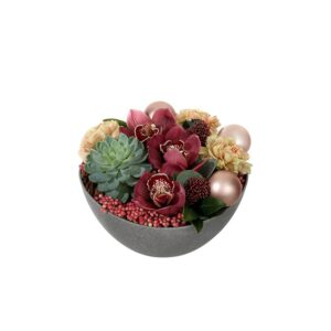 Liten juldekoration i rund skål, med vinröda orkidéer, rosépeppar, julkulor och grönt. Juldekorationen ingår i Interfloras julsortiment.