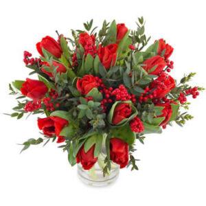 Bukett med röda jultulpaner, röda bär och gröna blad. En bukett från Euroflorist.