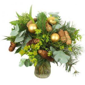 Festlig bukett med naturen som bas. Guldkulor som dekoration. Blommorna hittar du hos Florister i Sverige.