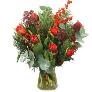 Julbukett med röda jultulpaner, röda bär och grönt. Grymt fin! Skicka blommorna med bud från Florister i Sverige!